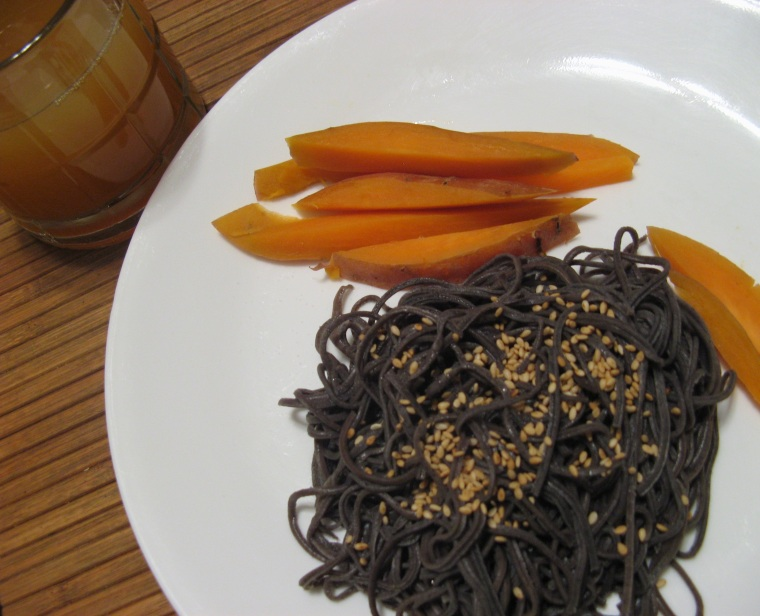 Black bean noodles, topped with sesame seeds, and paired with sweet potatoes and apple cider.